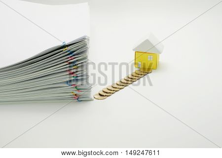 Pile overload paperwork with colorful paperclip and pile of gold coins with house on white background.