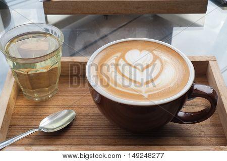 hot milk art coffee on wooden plate
