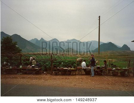GUILIN / CHINA - CIRCA 1987: Roadside vendors sell fresh produce by the road in Guilin.