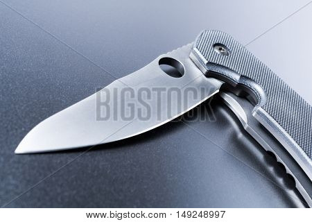 Macro Of A Lying Half Opened Faint Military Knife On Dark Ground
