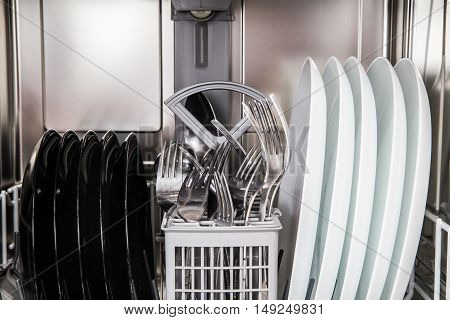 Steel Forks And Plates In Modern Dishwasher Machine