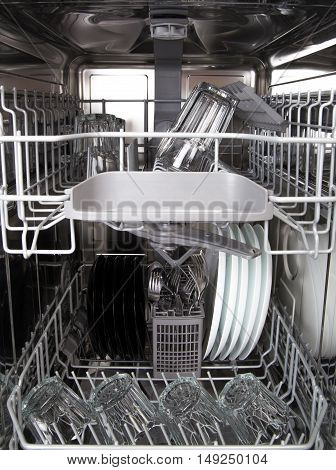 Glasses And White Plates In A Modern Dishwasher Machine