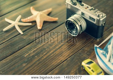 camera and starfish on wooden table with copy space travel concept vintage tone soft focus