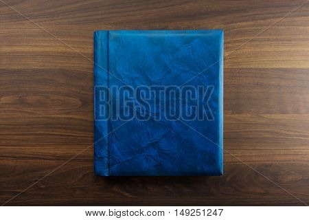 Blue faux leather Photo album or Year book cover, blank, placed on a dark colored wooden table.