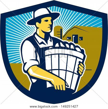 Illustration of an organic farmer carrying basket of harvest crops looking to the side set inside shield crest with barn and sunburst in the background done in retro style.
