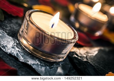 Two Romantic Candlelights On Slate With Rose Petals And Leafs