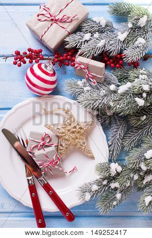Christmas table setting. White plate knife and fork napkin and christmas decorations in white and red colors on blue wooden table. Selective focus.