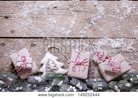 Christmas decorations. Border from presents fur tree branches and decorative toy on aged wooden background. Place for text. Selective focus is on toy.