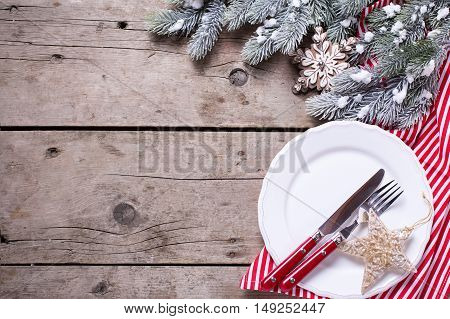 White plate knife and fork napkin and christmas decorations in white and red colors on aged table. Top view. Place for text. Selective focus.