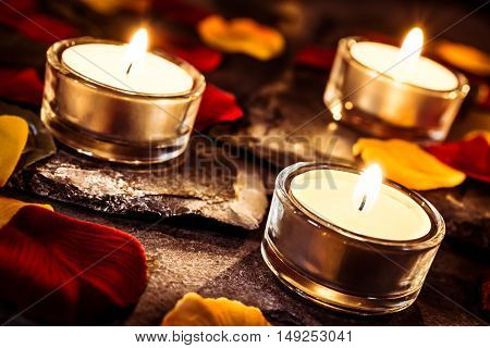 Three Romantic Tealights On Slate With Rose Petals And Leafs
