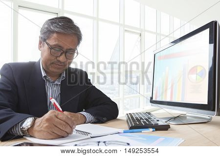 asian senior business man working on computer table for office life theme