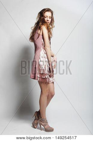 Full length portrait of beautiful fashion model posing in studio on white background