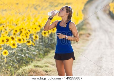 Beautiful Young Woman Drinking Water After Running In Countryside.