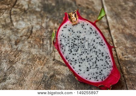 Pitahaya or dragon fruit on the wooden board. Cross section of a ripe white pitahaya