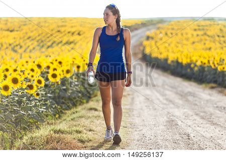 Beautiful Young Woman Resting After Running In Countryside.