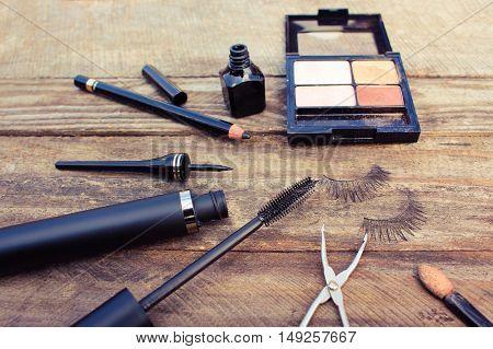 Cosmetics for eyes: pencil, mascara, eyeliner, false eyelashes and eyeshadow. Toned image.