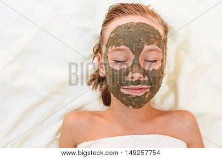 Beautiful young girl with facial clay mask.
