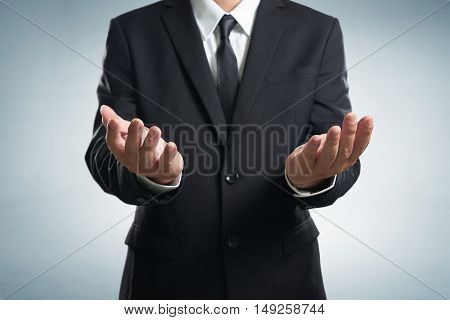 Businessman in black suit lending a helping hand isolated on white background