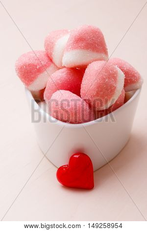 Sweet food candy. Pink jellies or marshmallows with sugar in white bowl on wooden table decorated with red heart love symbol