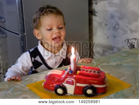Boy three years blows out a candle on a birthday cake in the birthday