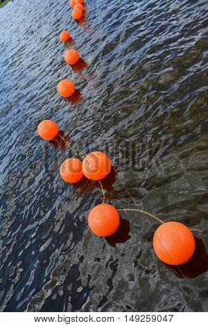 Line of orange buoys on resort lake water