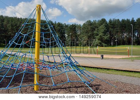 Volleyball net and playground equipment on sunny summer day