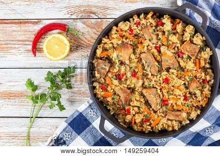 Homemade prepared paella with meat pepper vegetables and spices in iron pan on white peeling paint wooden planks chili pepper lemon slice and parsley on background view from above