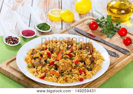tasty paella with meat pepper vegetables and spices on platter on cutting board lemon slice spices and cherry tomatoes on background view from above close-up