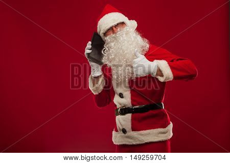 happy santa claus talking on mobile phone and show okay gesture. on the red wall background