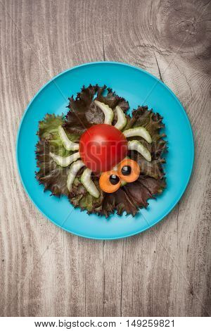 Spider made of vegetables on plate and board