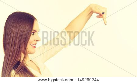 Woman showing presenting long haired fashionable girl pointing with finger at copy space text area. Fashion advertisement concept. Studio shot on bright background