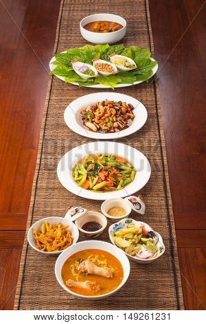 Multiple Thai food dishes on long dark wooden table