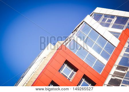 Part facade of the house red in the high-tech style with refractive glass windows on a bright sunny cloudless day