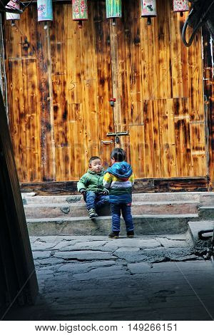 FengHuang - 28 December 2014: Lovely boys enjoy at ancinent town in morning together,FengHuang,Hunan,China