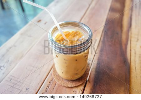 Glass of cold coffee on brown wood table at cafe.