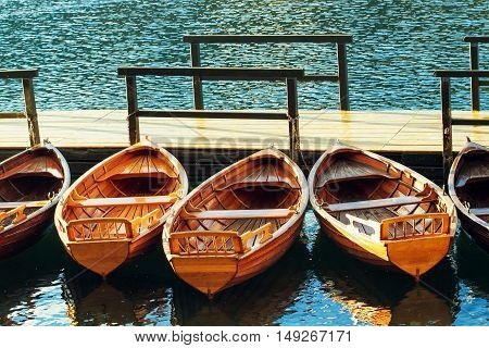 Small wooden boats docked and tied to empty pier on the lake