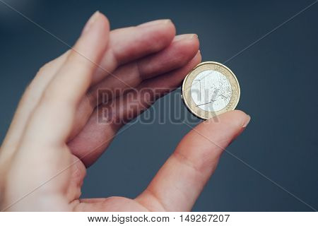 Business woman holding one euro coin between fingers close up with selective focus