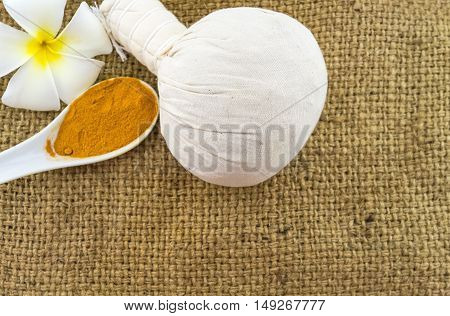 Spa herbal compressing ball white frangipani flowers (Plumeria spp Apocynaceae Pagoda tree Temple tree) and turmeric powder in wooden spoon on brown sack fabric background