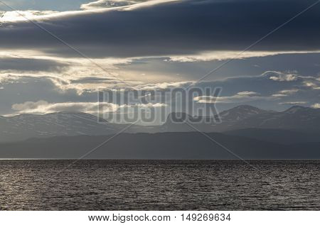 View of a lake and mountains in late evening. Overcast and some wind.