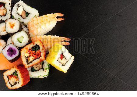 Mixed sushi rolls on a slate stone background