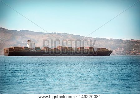 Large container ship, which sails on the open sea from the port of San Giovanni in southern Italy