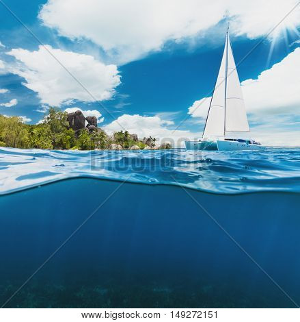 Catamaran boat sailing next to tropical island in Seychelles