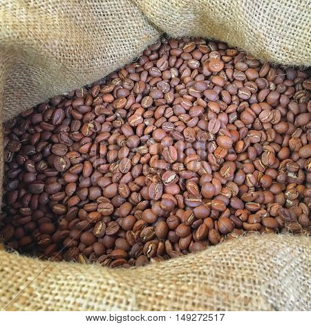Natural brown and well-roasted coffee beans in a wooden bowl