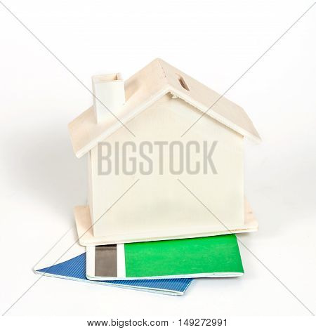 Miniature house with book bank on white