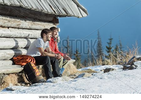 Two friends are having rest on wooden bench in winter mountains outdoors