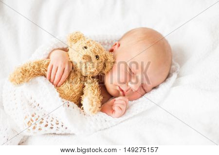 Newborn baby girl sleeping with teddy bear