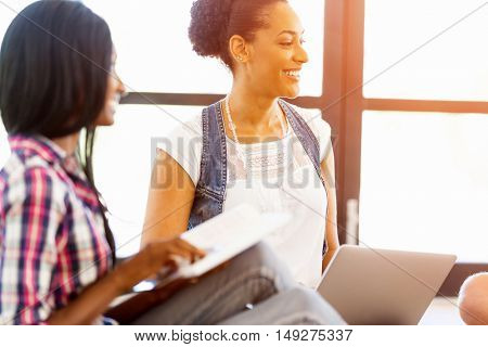 Portrait of smiling afro-american office worker in offfice with her colleague