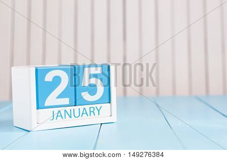 January 25th. Day 25 of month, calendar on wooden background. Winter concept. Empty space for text.