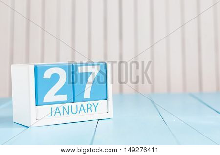 January 27th. Day 27 of month, calendar on wooden background. Winter at work concept. Empty space for text.