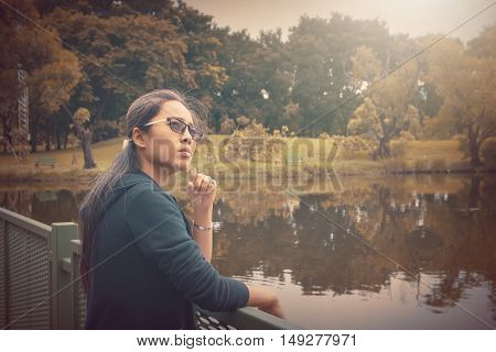 thoughtful woman Standing alone outdoors fantasy effects applied.